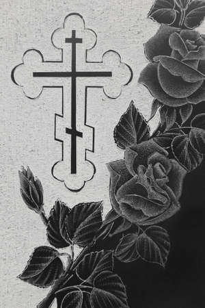 black granite gravestone with engraving picture, roses ornament and christian cross photo