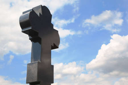 black granite cross on cemetery, blue sky with clouds photo