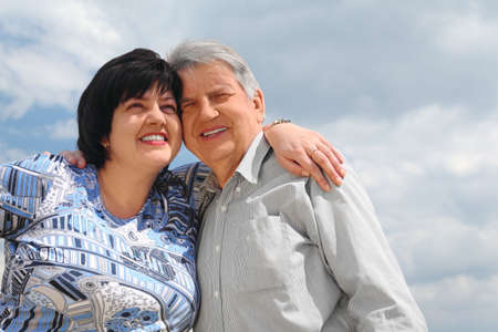 heir: old senior and his adult daughter embracing and smiling, sky with clouds Stock Photo