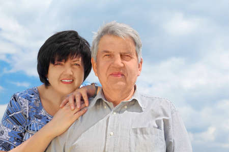 portrait of old senior, his adult daughter leaning to his shoulder and smiling, sky with clouds, focus on man photo
