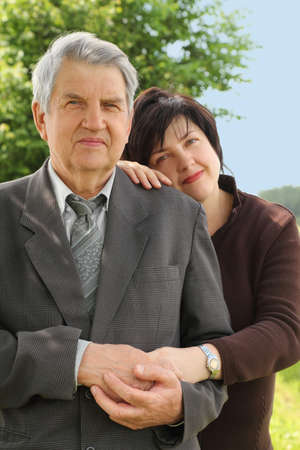 portrait of old senior in suit, his adult daughter leans on his shoulder, smiling, summer trees and sky
