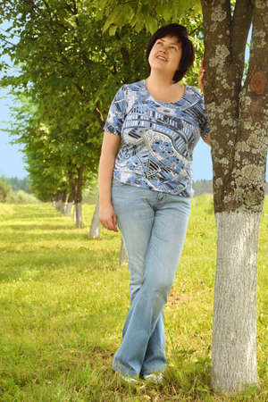 plumpy brunette woman standing on lawn near tree, smiling and looking at side, summer Stock Photo