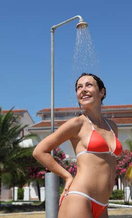 personas tomando agua: Mujer hermosa joven que llevaba un traje de ba�o rojo toma una ducha Foto de archivo