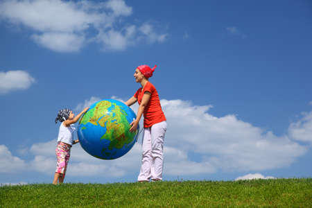 Mother with daughter stand on  grass and hold  large inflatable ball as  globe photo