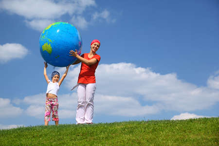Girl lifts an inflatable globe upwards and  mother  helps daughter to hold him, upright on  grass photo