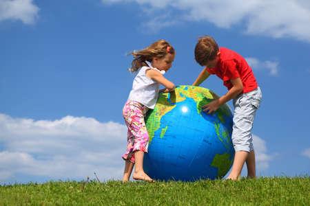 amor al planeta: Hermano hermana con soporte en la hierba y el mapa de estudio sobre un globo inflable