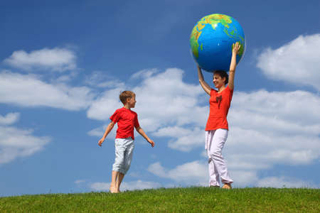 Mother stands on  grass and holds hands  large inflatable ball on  head,  boy comes running to it photo