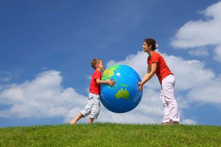 madre tierra: Madre con hijo jugar un globo inflable en el stand de día en la hierba