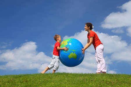 Mother with  son play an inflatable globe in  day-time stand  on  grass photo