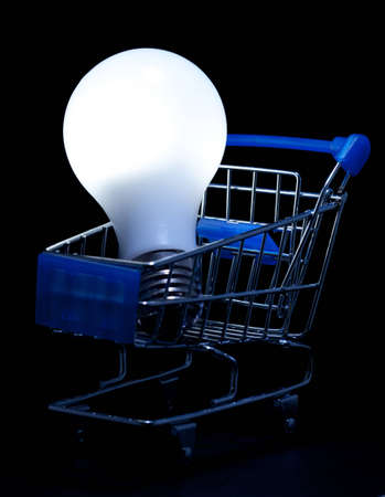 Shopping cart with lightning light bulb on black background. photo