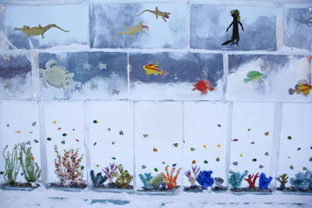 Ice composition 'Aquarium' with small fishes and seaweed