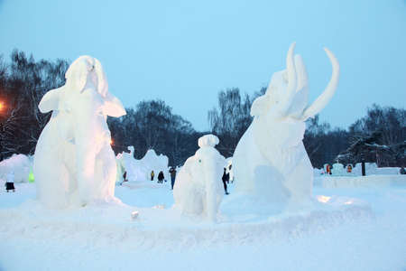 People walk and are photographed against snow sculptures of elephants