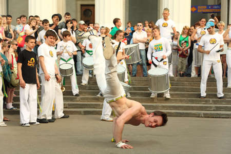 combines: MOSCOW - MAY 15: Man dance on real capoeira performance at All-Russia Exhibition Center on May 15, 2010 in Moscow, Russia. Capoeira combines elements of martial arts, music, and dance
