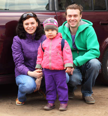 hunker: Family, mother, father and child, in outwear hunker down in front of car and smile