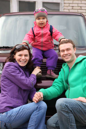 hunker: Happy family in outwear - mother and father hunker down in front of car and support little daughter sitting on car Stock Photo