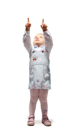 Little blond girl in jean sundress points two fingers up and looks up photo