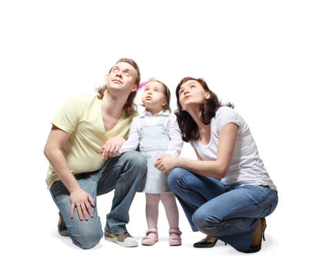 Mother, father and little daughter sit down, hold hands and fixedly looking up Stock Photo - 12734219