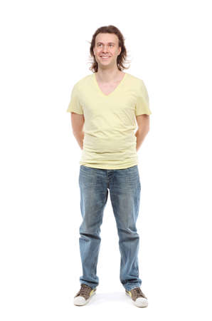 paunch: Full length portrait of adult man over 30 years with hair to shoulders in a shirt, jeans and sneakers with a little paunch, which has removed hands behind back, looking up and smiling