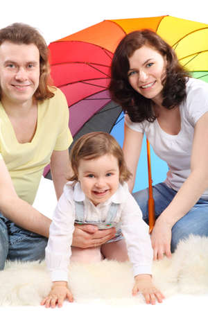 Happy young family - mother, father and little daughter - are sitting under colored umbrella on a white fluffy fur, father embraces daughter photo
