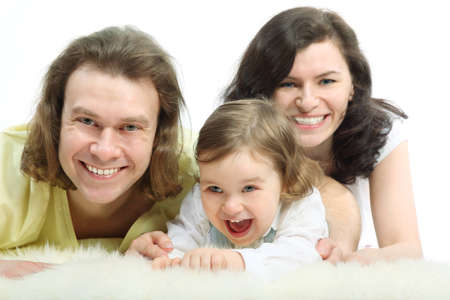 Happy young family - mother, father and playful little daughter - are lying on a white fluffy fur and laughing Stock Photo - 12732019