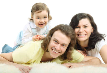 Happy young family - mother and father lie on a white fluffy fur and daughter lie on father and laugh Stock Photo - 12731919
