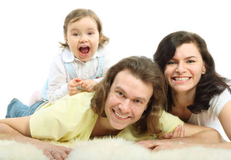 Happy young family - mother and father lie on a white fluffy fur and daughter lie on father and laugh with mouth open Stock Photo - 12731929