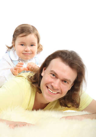 Happy little daughter sits on father which lying on the white fur carpet Stock Photo - 12731777