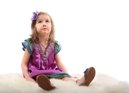 Little blond girl sitting on a fluffy carpet and thoughtfully looks up photo