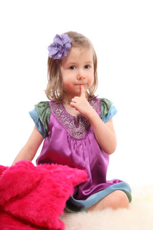 Little blond girl sitting on a fluffy carpet with pink fur coat Stock Photo - 12731844