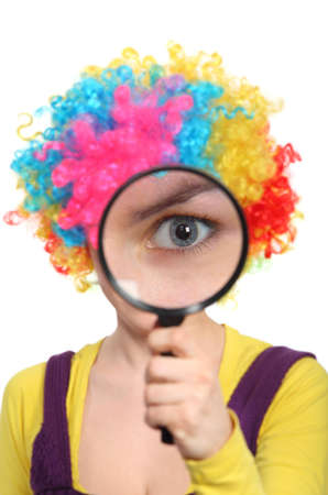 Girl in colored curly wig looking through a magnifying glass  photo