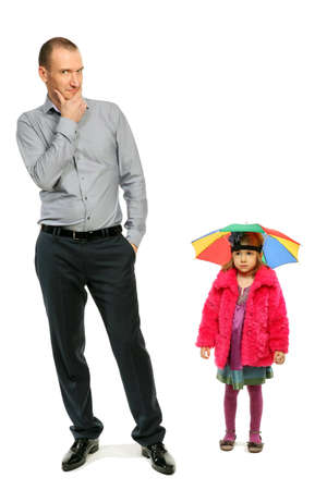 Thoughtful businessman stands apart from stylish little girl in pink coat and hat-umbrella Stock Photo - 12731733