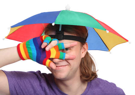 Portrait of happy man with rainbow hat umbrella on head and colorfull glove photo