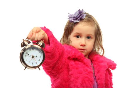 Little glamour girl in pink coat shows time on round alarm clock Stock Photo - 12731776