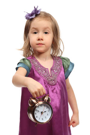 Little glamour girl in stylish dress shows time on round alarm clock Stock Photo - 12732015