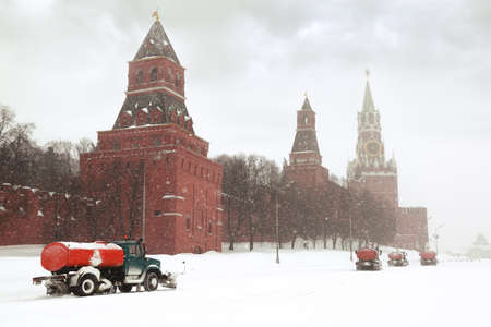 Four snow-remover trucks on the road near Kremlin chiming clock of the Spasskaya Tower in Moscow, Russia at wintertime during snowfall