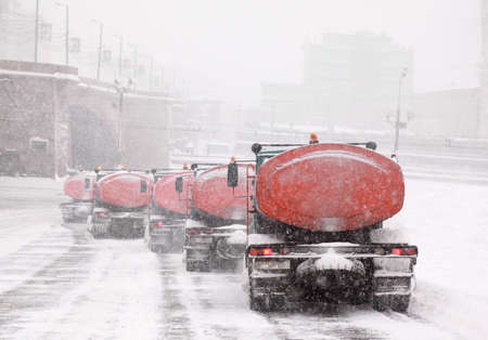 Column of five snow-remover trucks on the road in Moscow, Russia at wintertime during snowfall