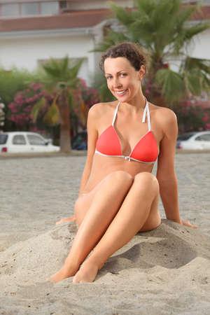 mandatariccio: young woman in orange bikini sitting on beach and smiling, house and palms