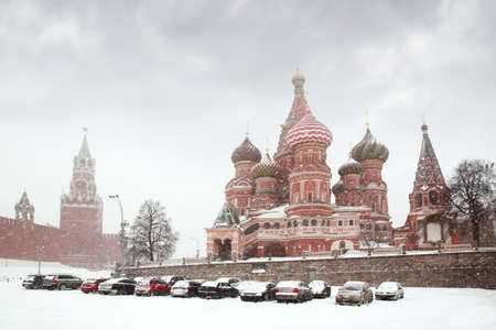 Car parking near Kremlin chiming clock of the Spasskaya Tower in Moscow, Russia at wintertime during snowfall