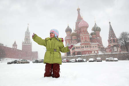Little girl catches snowflakes in front of background St. Basils Cathedral in Moscow, Russia at wintertime during snowfall photo