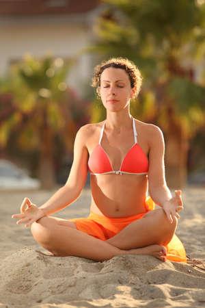 mandatariccio: young woman in orange bikini sitting on beach in lotus pose with closed eyes and meditating, palms