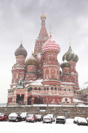 Car parking near St. Basil Temple in Moscow, Russia at wintertime during snowfall photo