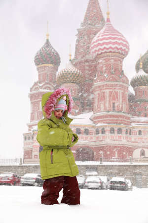 Little frozen girl standing in front of St. Basils Cathedral in Moscow, Russia at wintertime during snowfall photo