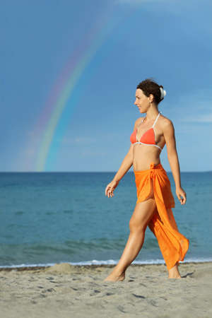 pareo: young brunette woman in orange bikini and pareo walking on beach and smiling, rainbow