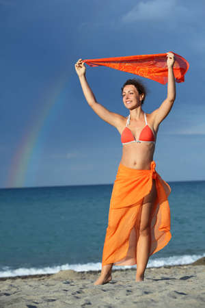 pareo: young brunette woman in orange bikini and pareo holding scarf over her head and smiling, rainbow  Stock Photo