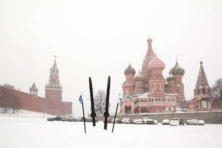 Cross-country skis and poles stuck in snow on Red Square near St. Basil Temple and Spasskaya Tower of Kremlin in Moscow, Russia at wintertime during snowfall