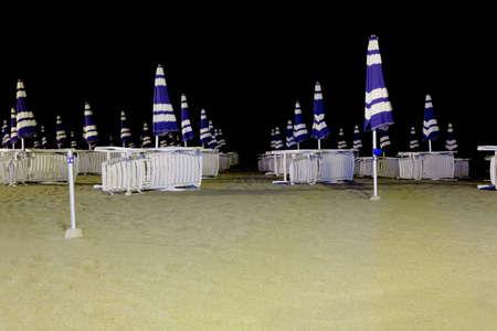 mandatariccio: many lounges and closed umbrellas on night beach, black sky Editorial