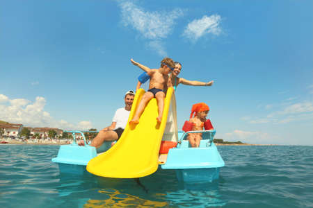 family with boy and girl on pedal boat with yellow slide in sea, view from water, shot from waterproof case Stock Photo