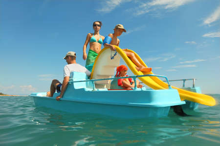 happy family with boy and girl on pedal boat with yellow slide in sea, view from water, shot from waterproof case Stock Photo