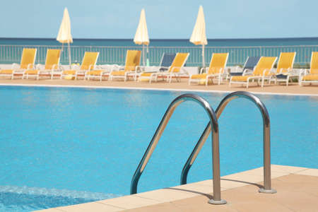 mandatariccio: hotel swimming pool with stair, yellow longes and umbrellas