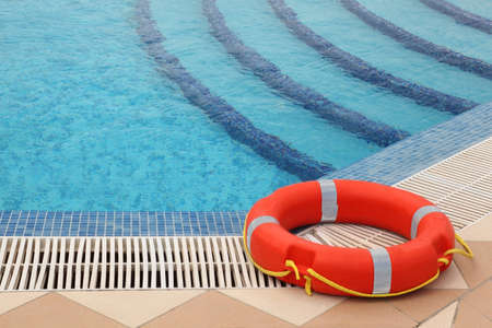 mandatariccio: red lifebuoy with yellow ropes on tiled floor near swimming pool with stairs